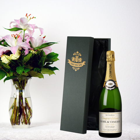 New Baby Personalised Champagne pictured next to a glass vase containing pink lillites