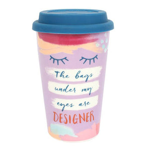 "Ceramic thermal travel coffee cup with ""The bags under my eyes are designer"" slogan and blue silicone rubber lid."