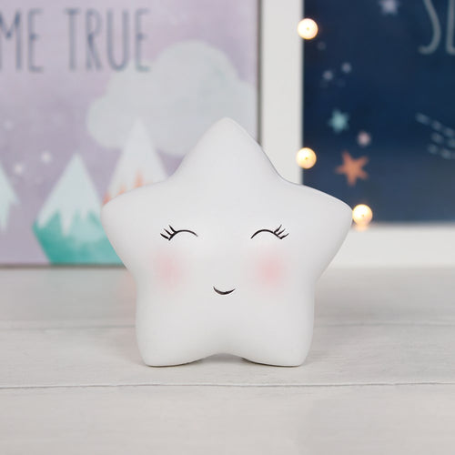 Freestanding white resin cute star ornament with smiley face, perfect for a shelf in a child's bedroom or nursery. Approx. size 7cm x 7.5cm