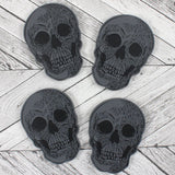 Set of 4 black wooden skull coasters.