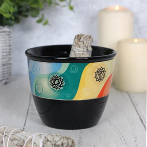 Black ceramic smudge bowl decorated with seven chakra healing symbols and colours