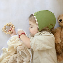 Baby in green bonnet sleeping with baby bracelet and natural wood bead teether Honeycomb Gift Set - Late Night Luna