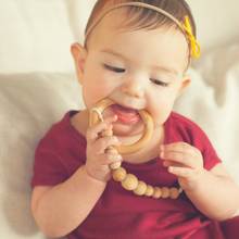 Baby girl in red chewing on teething ring attached to wood bead binky clip Honeycomb Wood Bead Pacifier Clip - Late Night Luna
