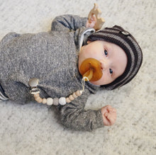 Baby wearing grey clothes and beanie with pacifier and grey white cream binky clip Harbor Crochet Wood Bead Pacifier Clip - Late Night Luna