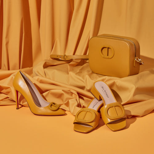 Still life image of shoes and handbags in yellow