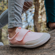 An image of a kid wearing Splay Explore™ Strawberry Milkshake pink and light gray shoes active shoes for kids.