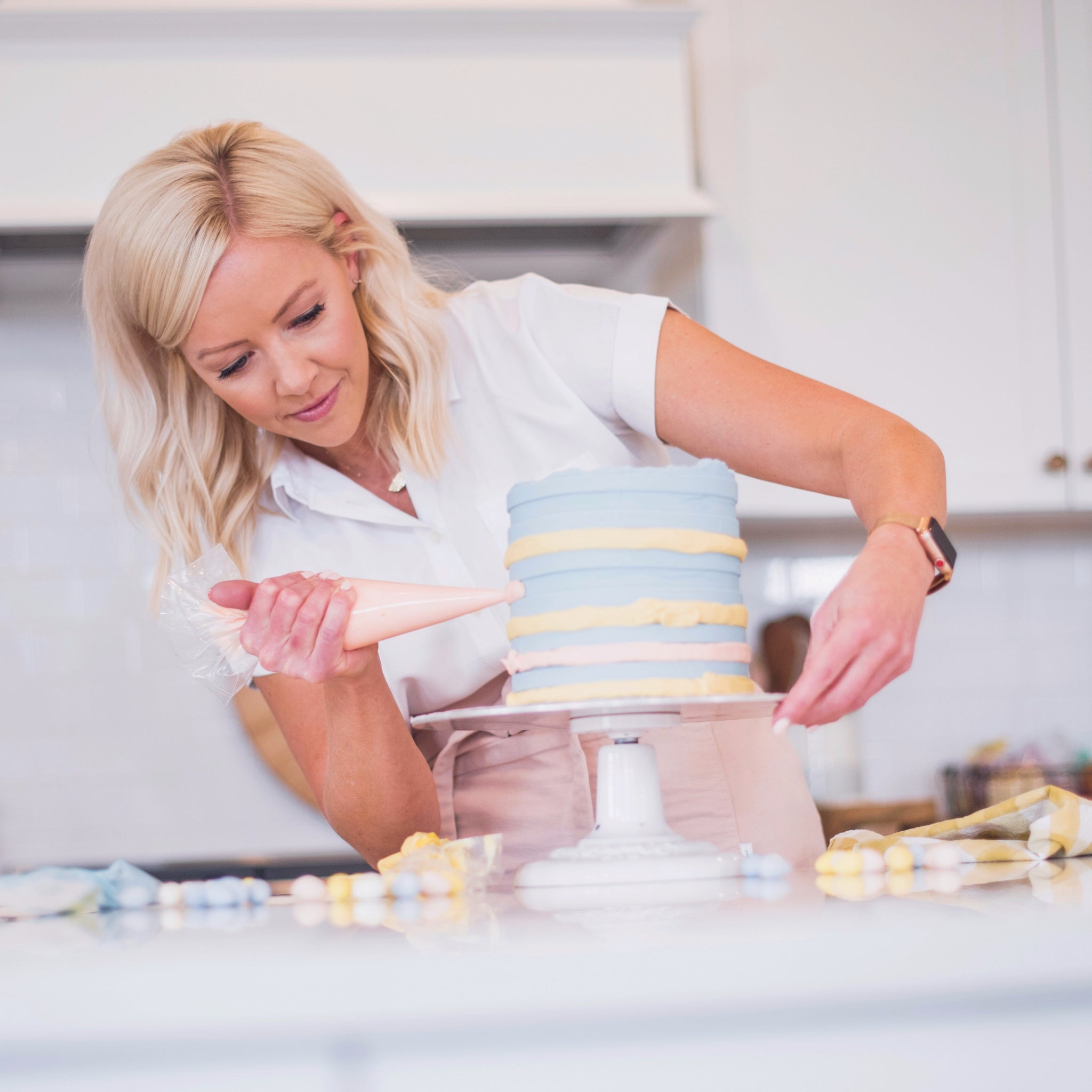 Courtney wearing a white shirt and pink apron icing a striped cake in her kitchen using her Pink Piping Bag which can be purchased on the website