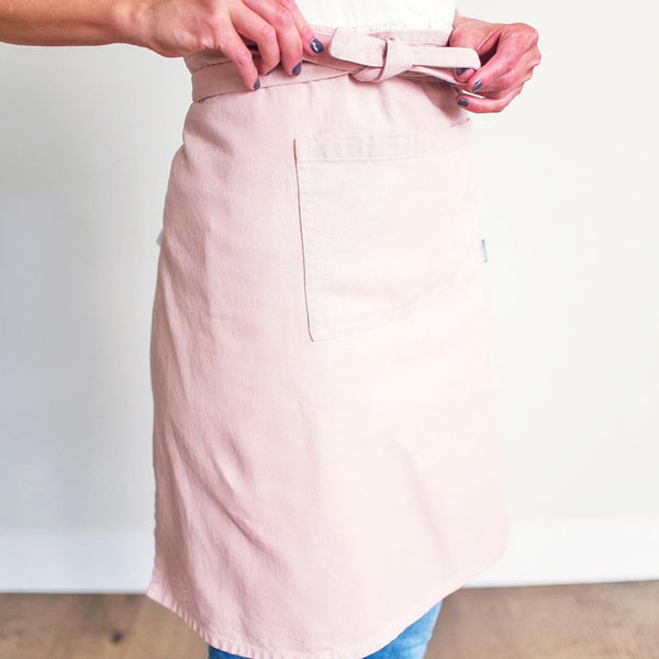 Courtney wearing the Pink Bistro apron and tying it around her waist