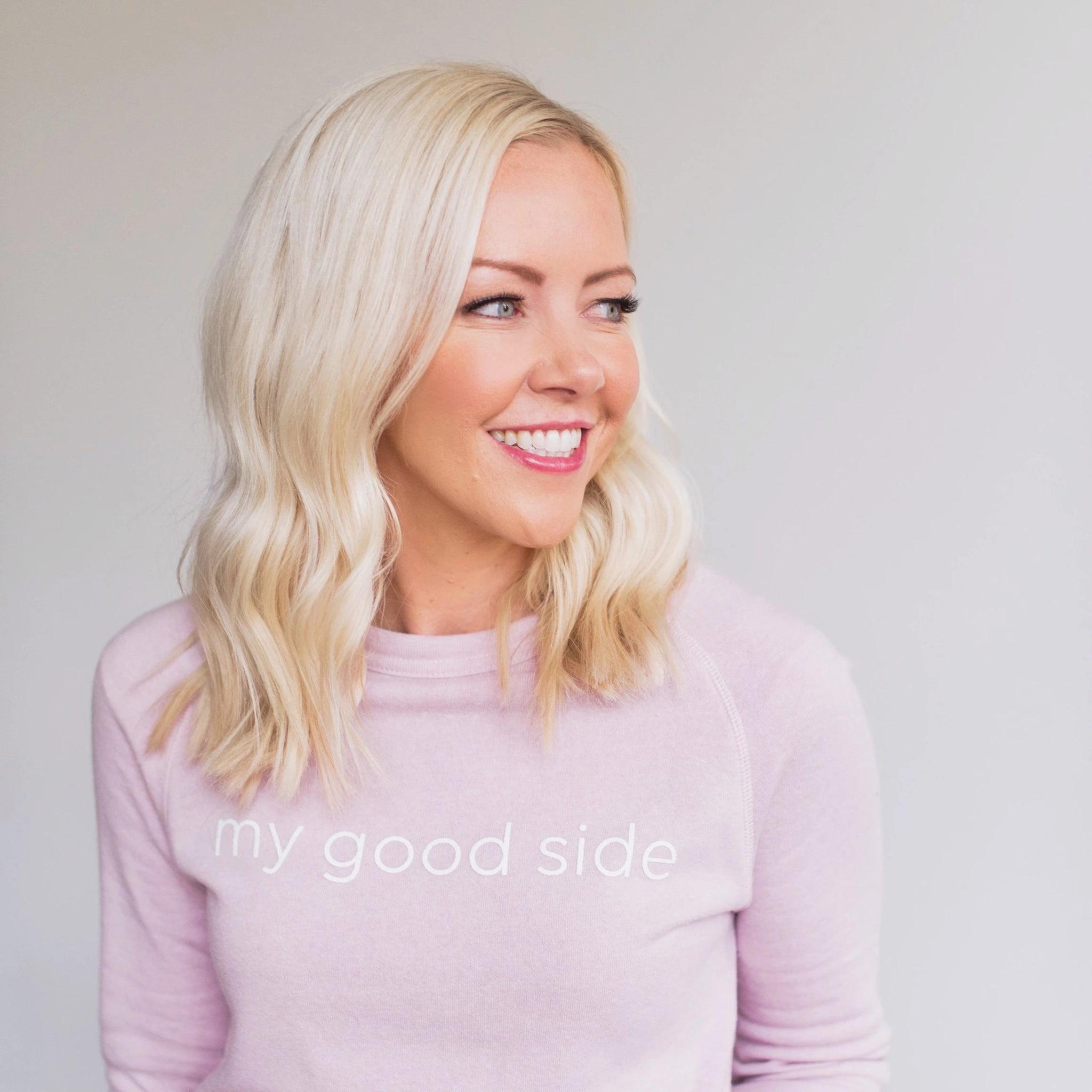 Courtney smiling to the side, wearing her light pink sweatshirt that says the words 'my good side' that can be purchased on the website