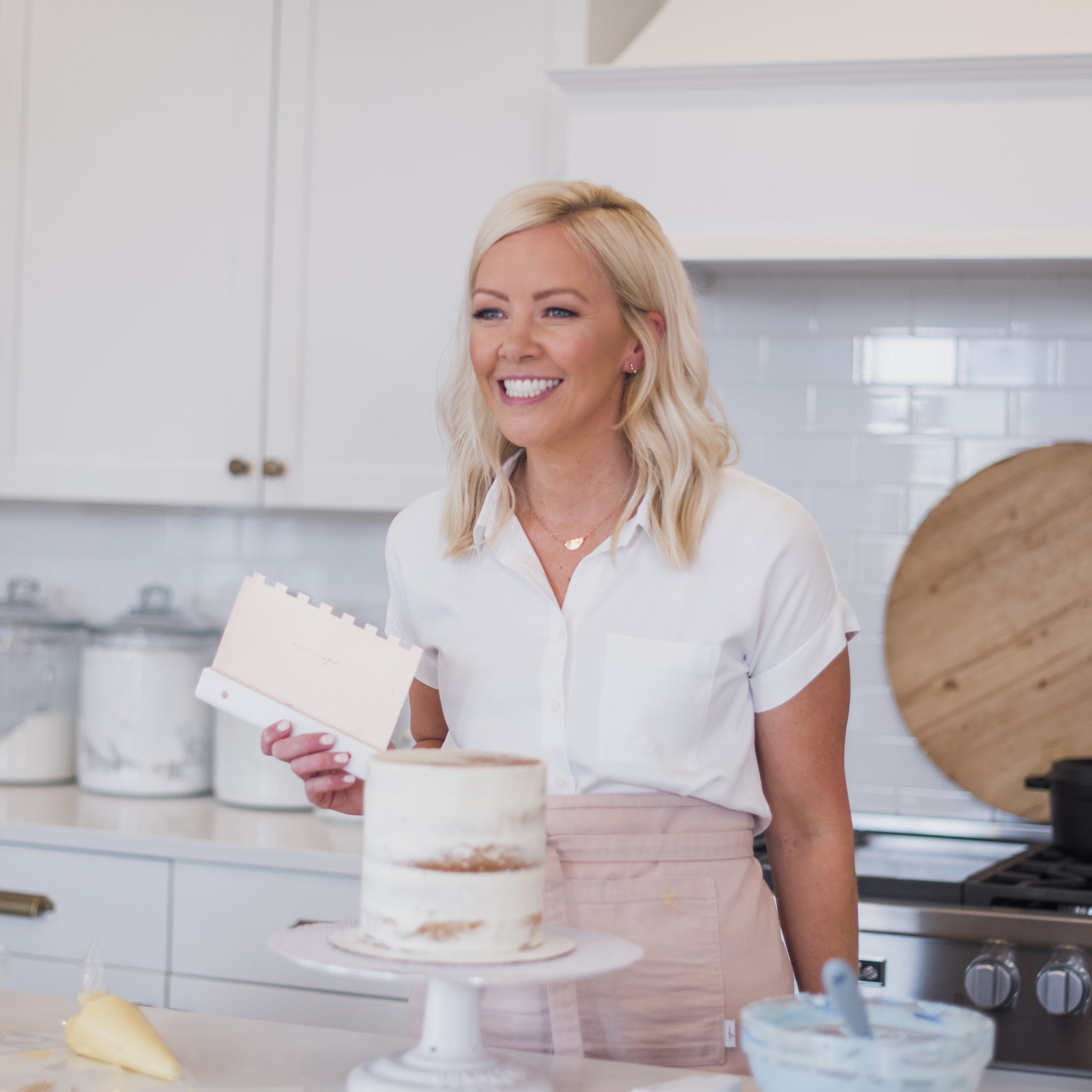 Courtney wearing a white shirt and pink apron with a cake in her kitchen using a scraper from the Texture Set which can be purchased on the website