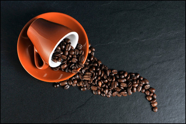 A blend of coffee beans spilling out of an orange cup and saucer.