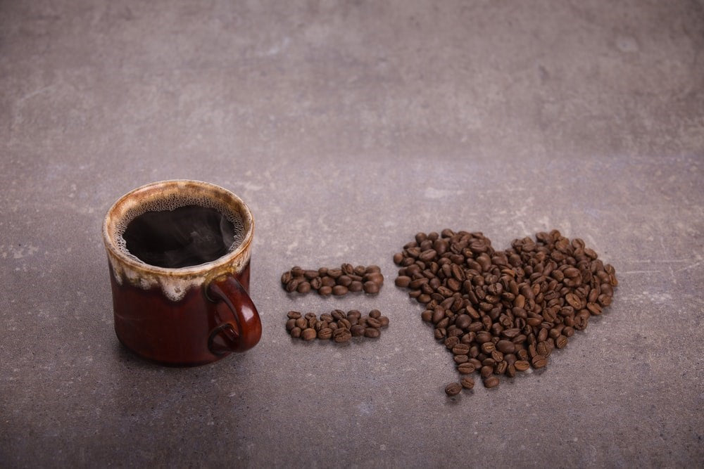 Coffee cup with coffee beans in the shape of a heart