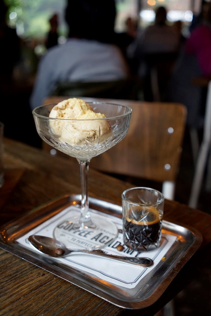 coffee ice cream in a glass bowl next to an espresso