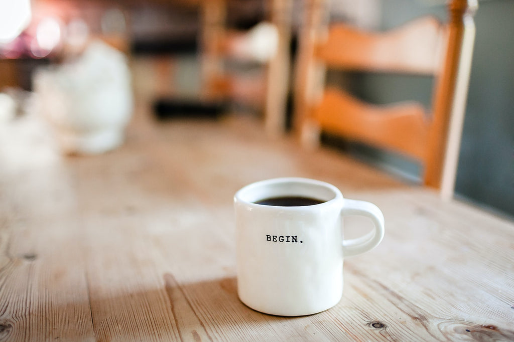 Coffee in a white mug with the word 'begin'