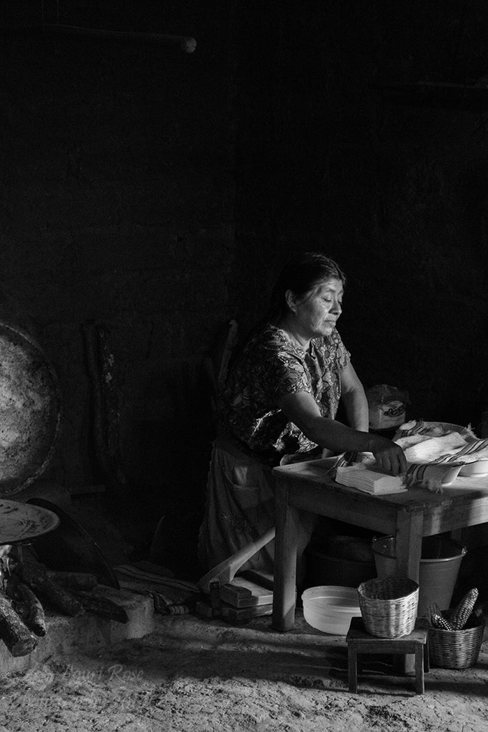 Black and White Photograph of woman cooking in Zincatan, Mexico.