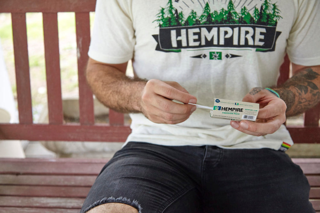 Man in hempire shirt rolling with Hempire papers