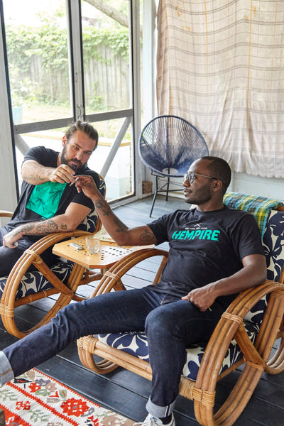 Two men sitting on a porch in Hempire Tees sharing a smoke.