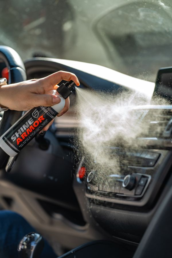 Person spraying Shine Armor Interior Cleaner to the dashboard of a car.