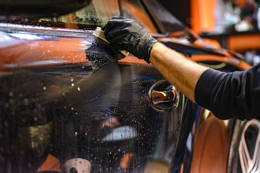 Man using an applicator brush to apply scratch remover to a car.