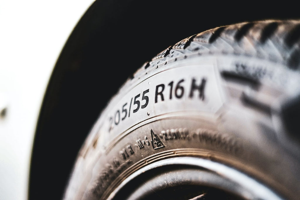 Close up of a tire and wheel on a car showing its rating