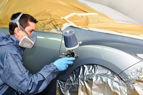 Man using a spray gun to apply paint to a silver cars front fender.