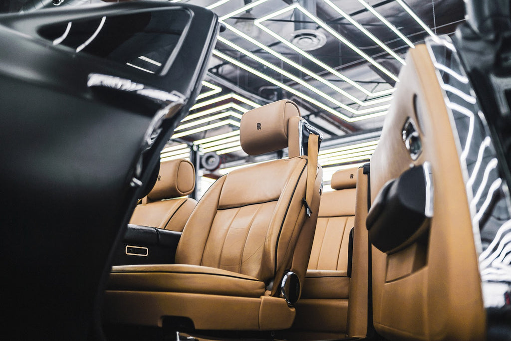 Brown leather car seats being installed into a car in a factory.