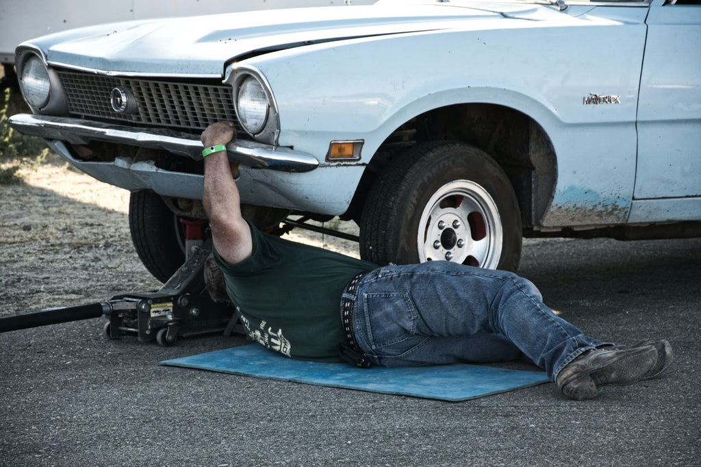 Man working to remove oil drain plug from a blue vintage car.