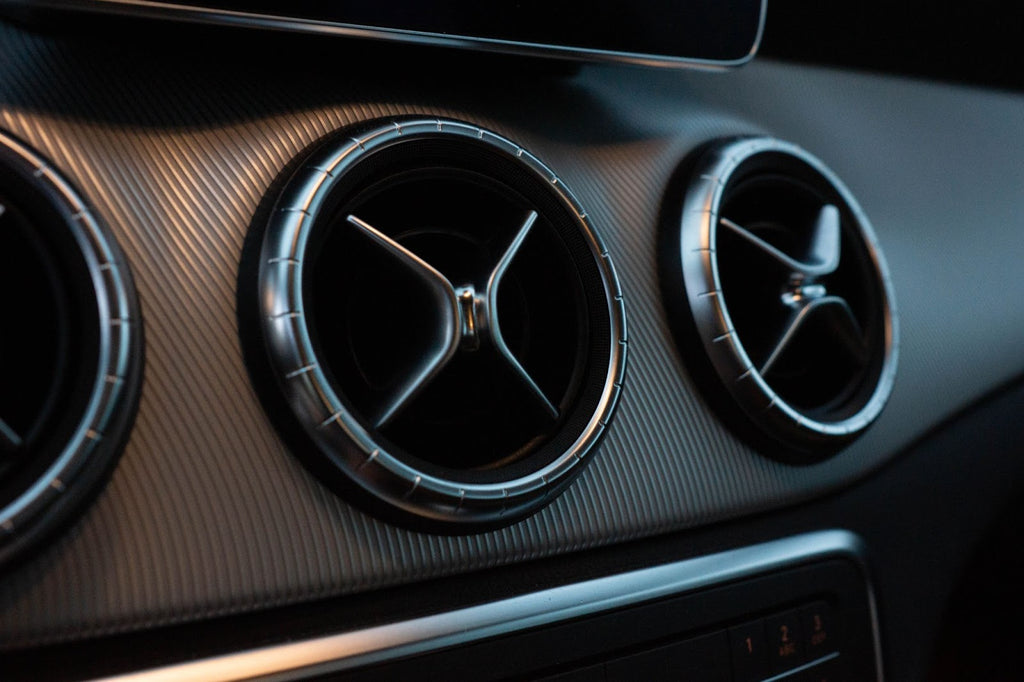 Air conditioner vent on the dash of a sports car.
