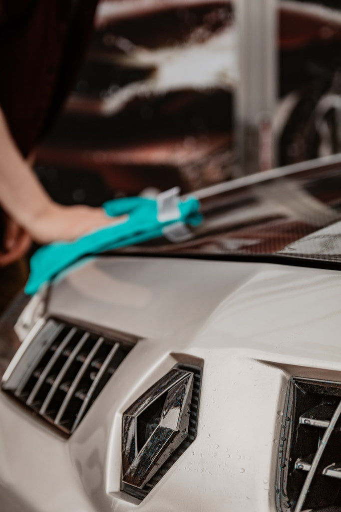 Person removing car wax with a blue microfiber cloth.