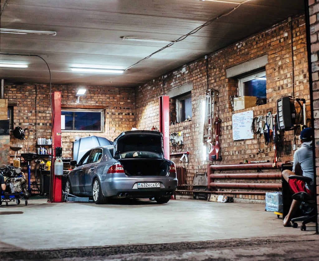 Car inside of a brick walled car garage with the trunk open.