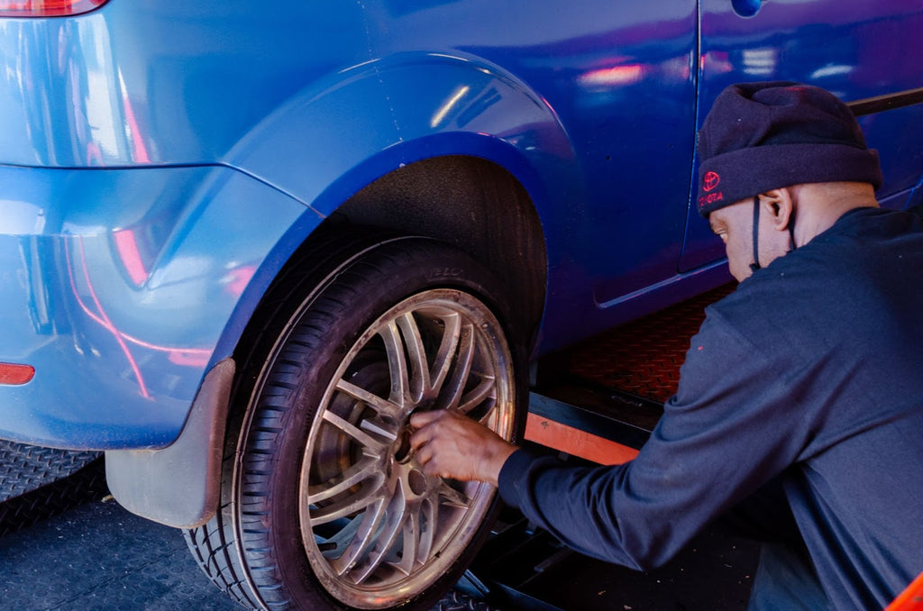 Man removing lugnuts from a gold rim on a blue car.