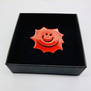 The Sun pin accessory The Extra Smile red