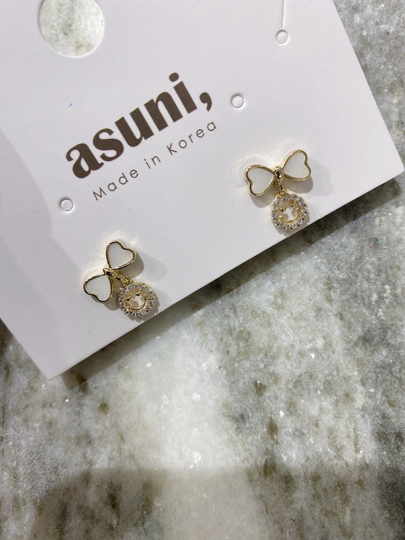 White Ribbon x Diamond Smile Earrings In Gold Tone