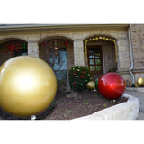 two shatterproof large Christmas ornaments in a garden