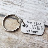 We Rise By Lifting Others Keychain
