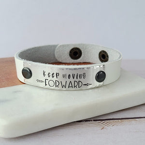 white leather cuff bracelet with metal plate that reads keep moving forward