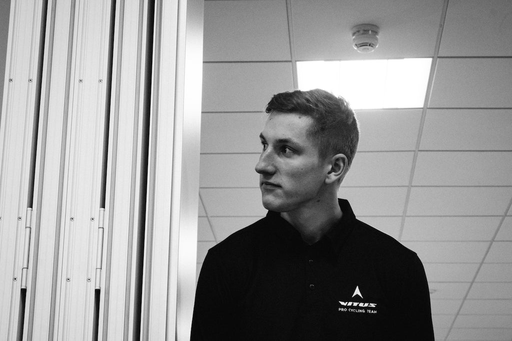 White male, twenties, black polo shirt, looking around the corner of a doorway, black and white image