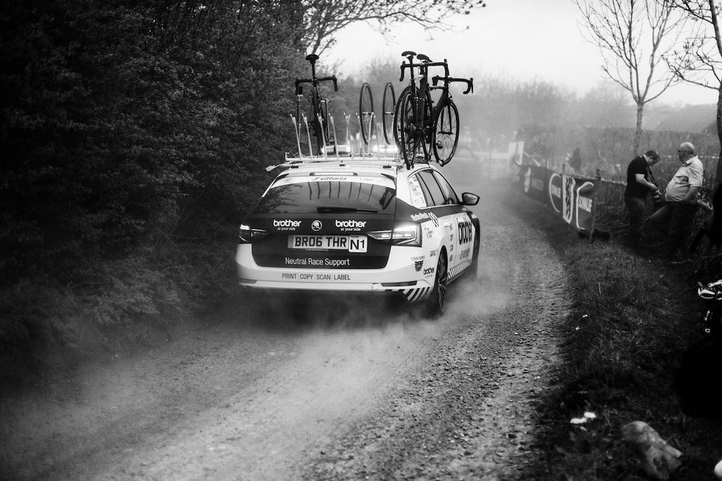 Car, rear view, black and white, driving away from camera, gravel lane, bikes on roof
