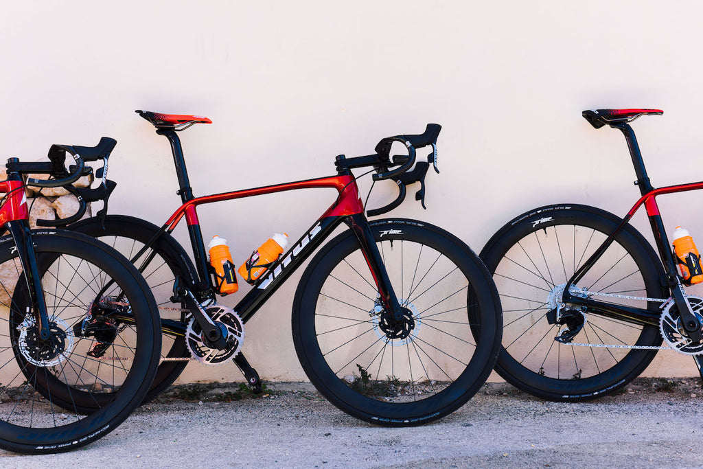 Racing bikes, black and red, three, leant against wall