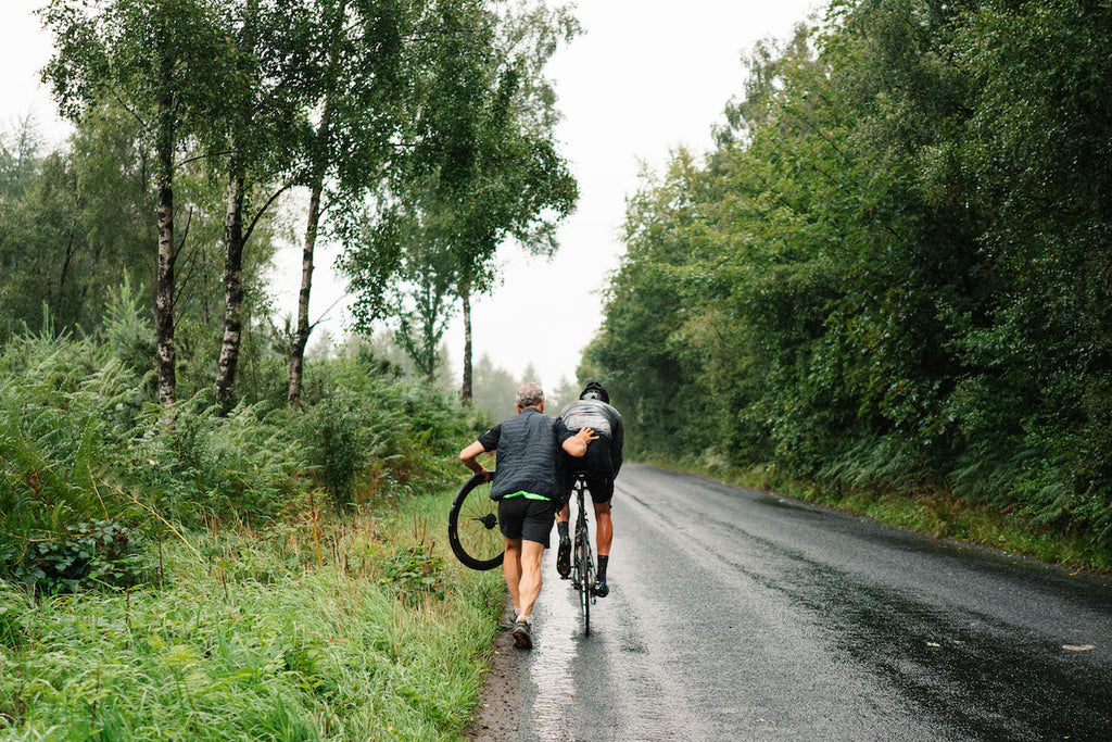 Man pushing cyclist with one hand, while holding bicycle wheel in the other. Country road. Rear view.