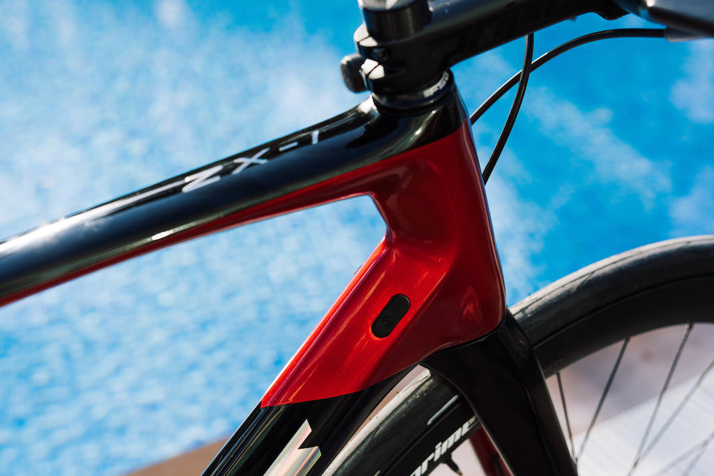 Racing bike, black and red, close-up, background is water in bright blue swimming pool