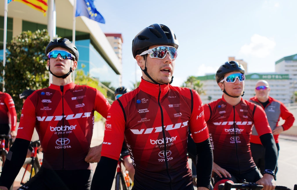 Racing cyclists, three, red jerseys, black shorts, black helmets, white glasses, stood outside hotel, sunshine