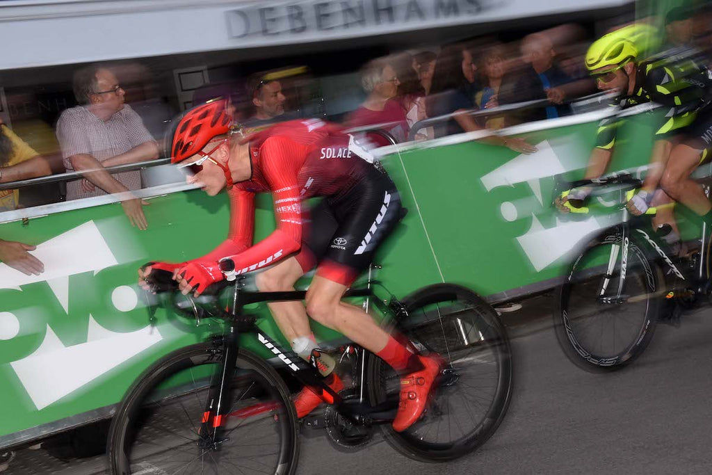 Racing cyclist, red jersey, black shorts