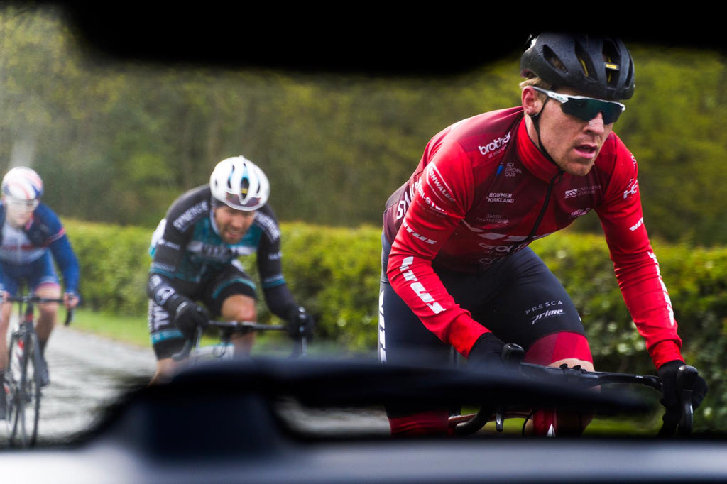 Racing cyclist, white, male, twenties, red jersey, black helmet, white-framed sports glasses, photographed from rear window of car