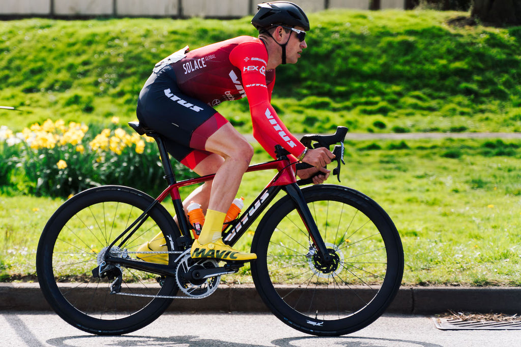 Racing cyclist, red jersey, black shorts, yellow shoes and socks, black helmet, red and black bike, side view, field in background
