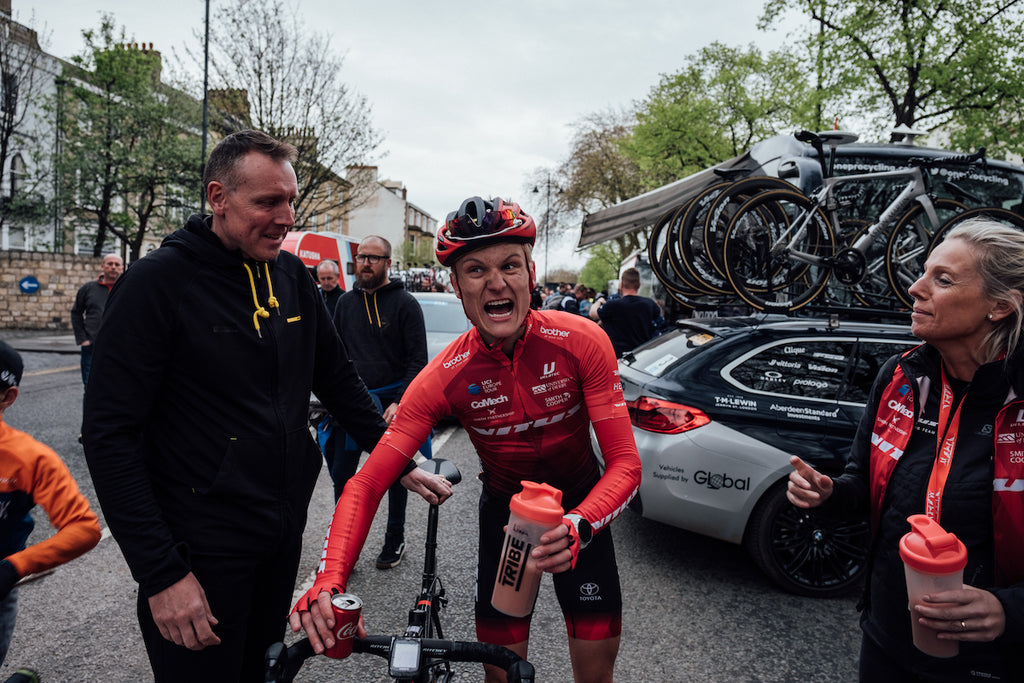 Racing cyclist, red jersey, black shorts, exhausted expression, pushing bicycle, flanked by helpers