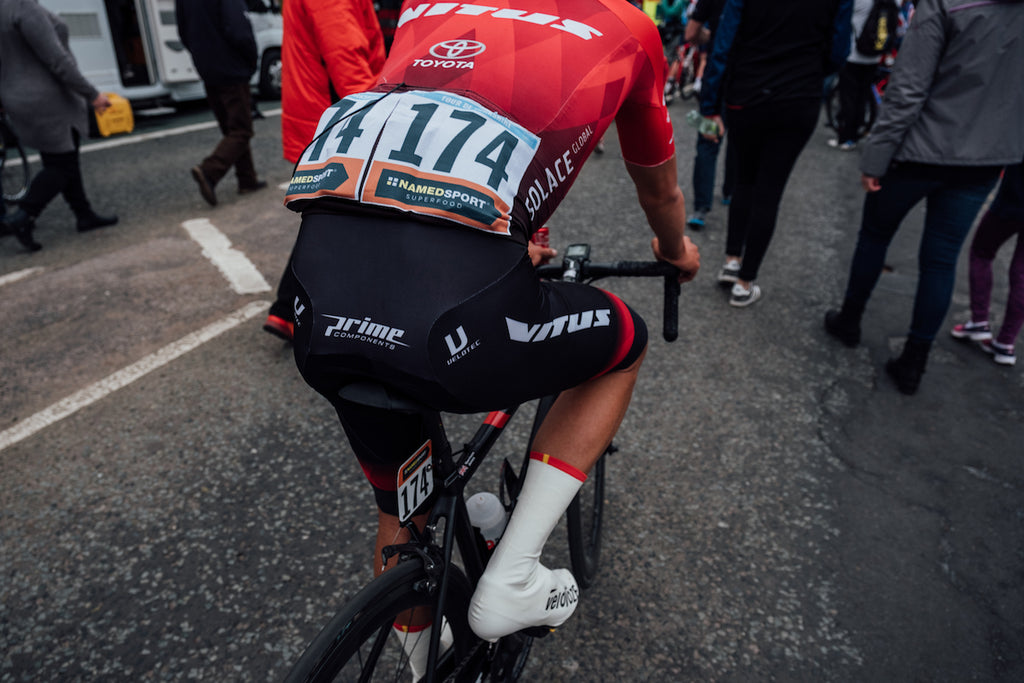 Racing cyclist, black shorts, red jersey