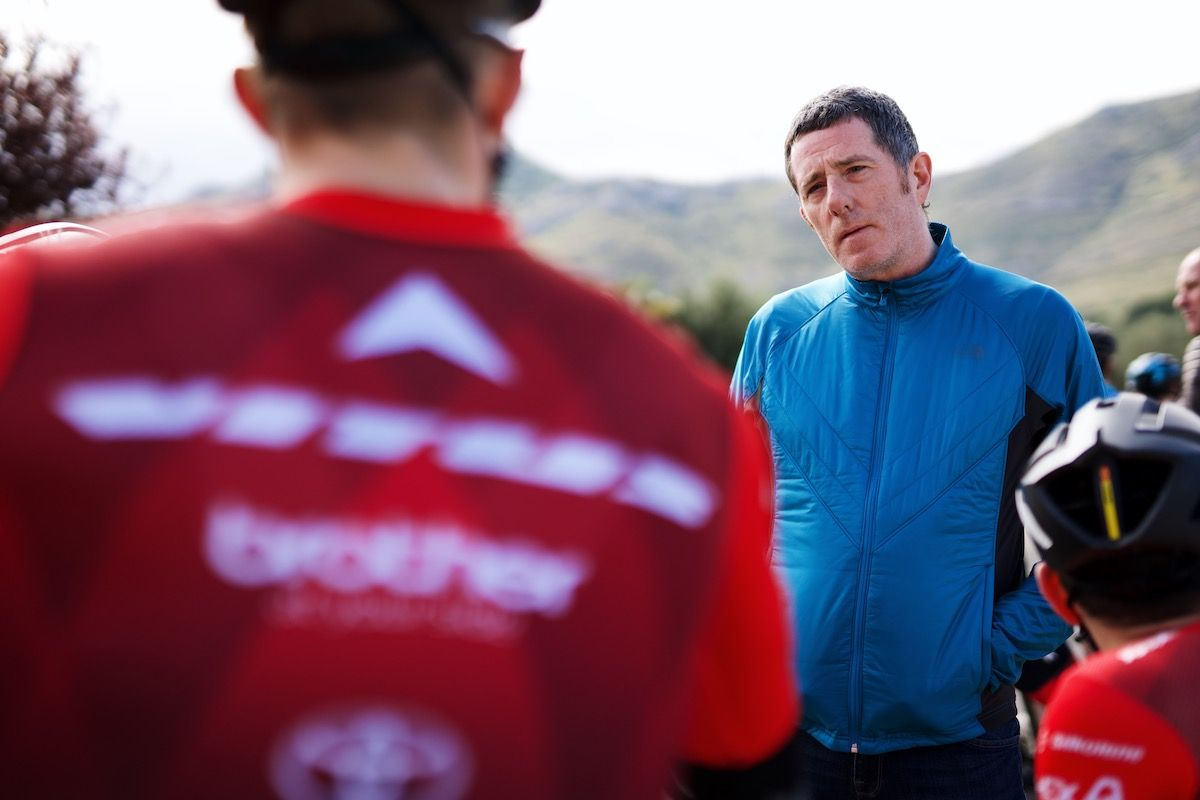 Man, white, fifties, black hair, blue jacket, talking to professional cyclist in red jersey