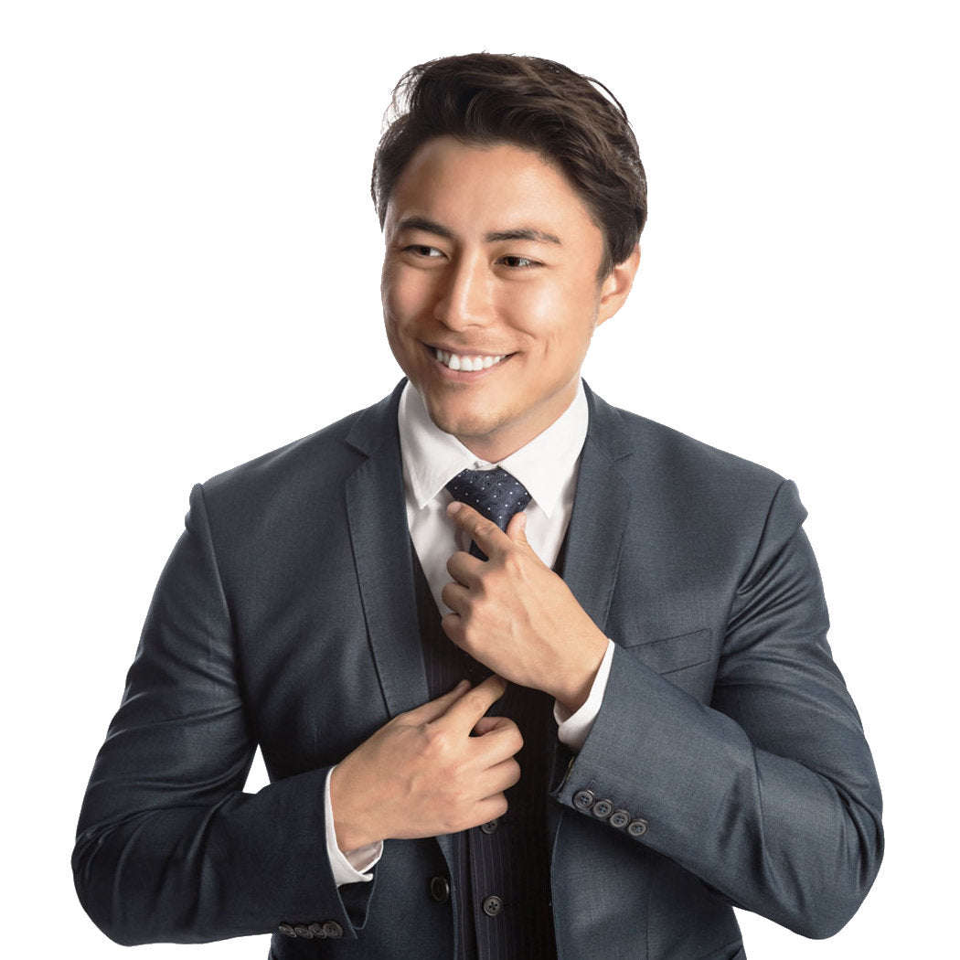 Young man in a suite adjusting his tie and smiling.