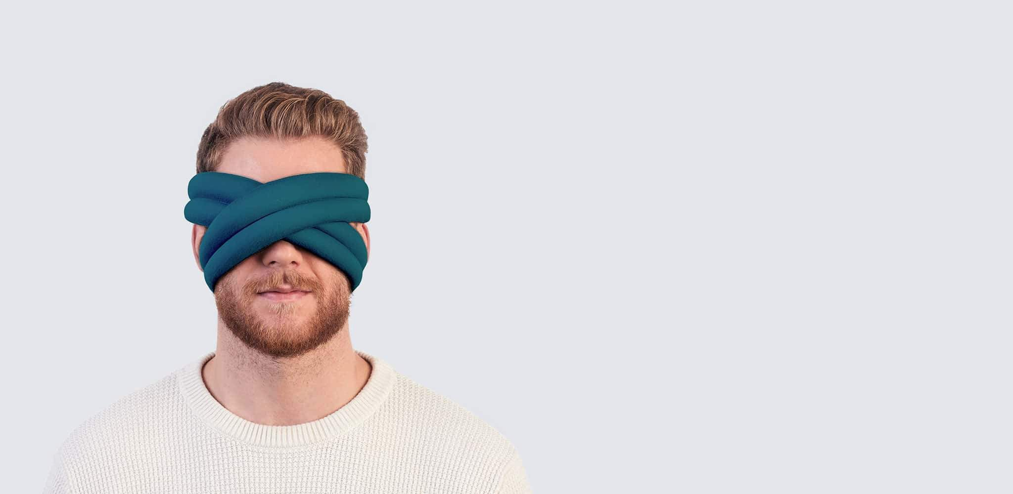 Man looking relaxed while wearing the OstrichPillow LOOP.